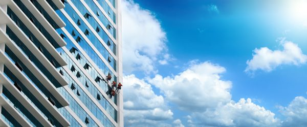 Group of workers cleaning windows on high rise building.Panoramic view